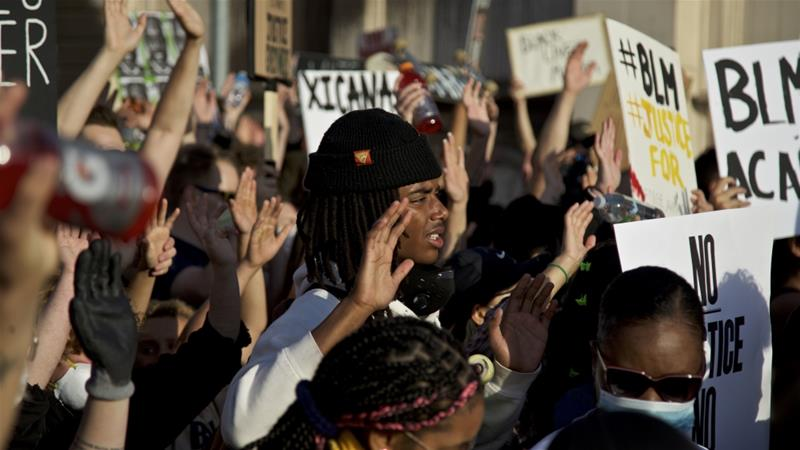 Demonstrators hold their hands up in Portland during a protest over the death of George Floyd, who died on May 25 after being restrained by police in Minneapolis [Craig Mitchelldyer/AP Photo] 
