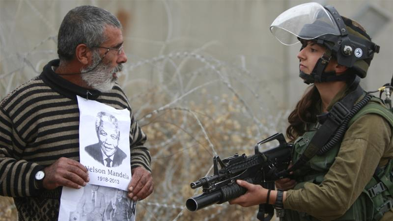 A Palestinian holds portraits of Nelson Mandela and Yasser Arafat during a protest at village of Bilin in occupied West Bank on December 6, 2013 [File: AP/Majdi Mohammed]