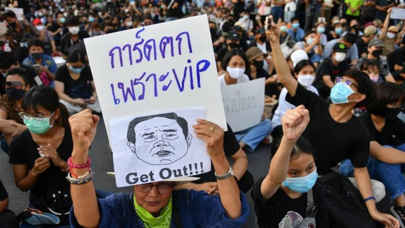 A protester holds a sign depicting Thai Prime Minister Prayuth Chan-ocha during a protest demanding the resignation of his government, while defying the coronavirus disease restrictions on large gatherings in the capital, Bangkok [Chalinee Thirasupa/Reuters]