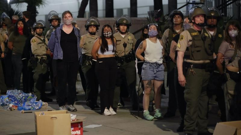 People who participated in a protest against the May 25 police killing of George Floyd are being arrested for curfew violation in downtown Los Angeles, June 3, 2020 [AP Photo/Marcio Jose Sanchez]
