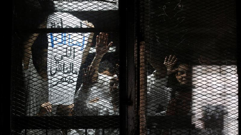 An Egyptian photojournalist looks on with others behind bars during their trial on the outskirts of Cairo [File: Amr Abdallah Dalsh/Reuters]