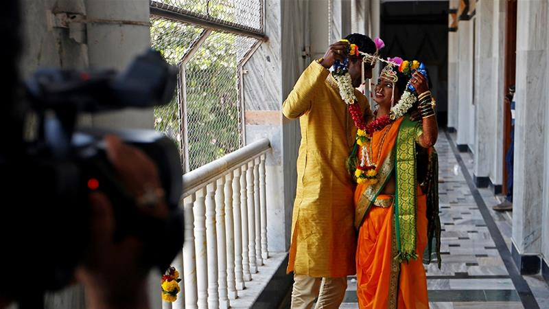 A Hindu couple poses for photographers after their wedding in Mumbai [File: Francis Mascarenhas/Reuters]