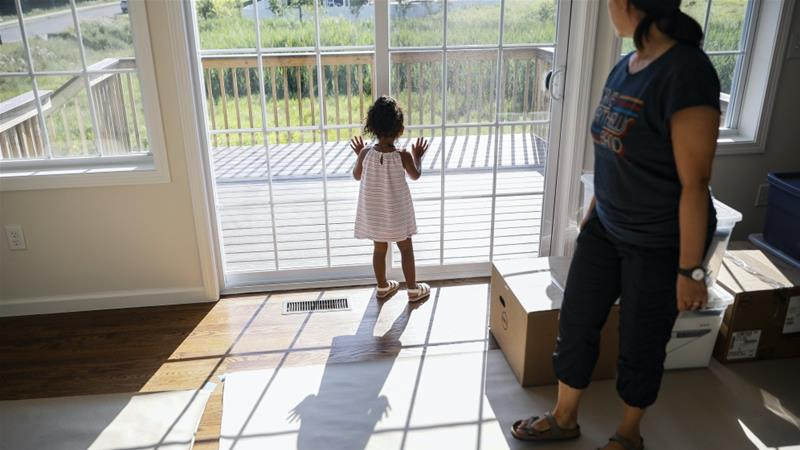 Joyce Lilly, right, watches her granddaughter Paige at their new home in Washingtonville, NY, where they recently moved from the Bronx after quarantining in their city apartment for three months  [File: John Minchillo/Reuters]
