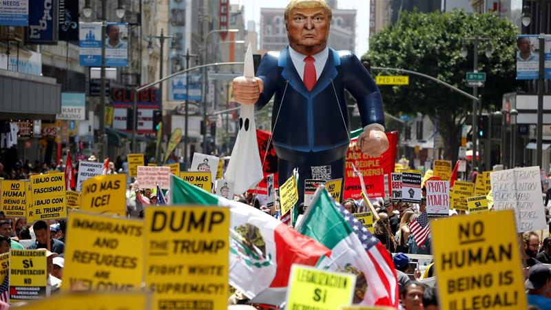People march with an inflatable effigy of Donald Trump during an immigrant rights rally in Los Angeles [File: Reuters]