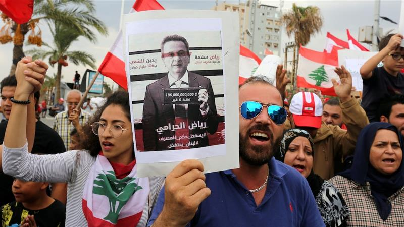 Demonstrators carry Lebanese flags and a banner depicting Lebanon's Central Bank Governor Riad Salameh [File: Aziz Taher/Reuters]