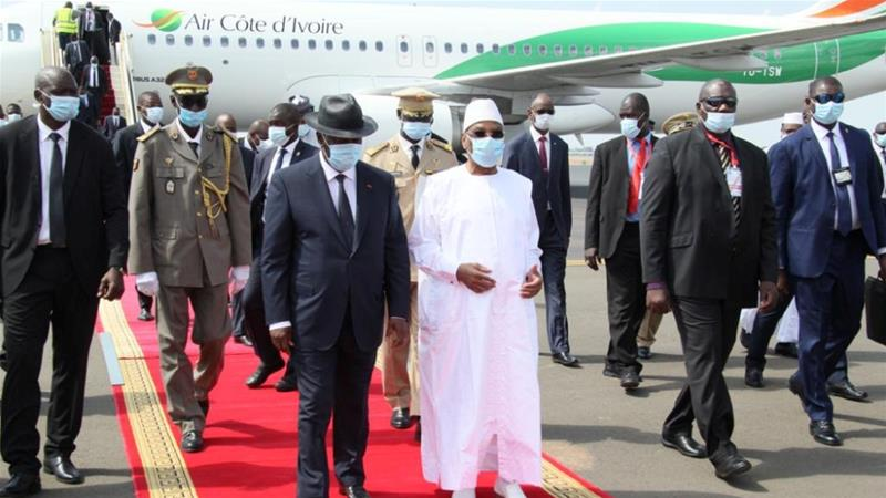 Mali's President Ibrahim Boubacar Keita (R) walks with Ivory Coast counterpart, Alassane Ouattara, upon his arrival in Bamako [Press Service of Prime Ministry/Handout via Reuters]
