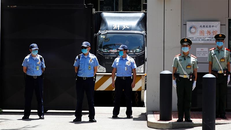 A removal van stands inside the US Consulate General in Chengdu as security personnel guard the front gate [Thomas Peter/Reuters]