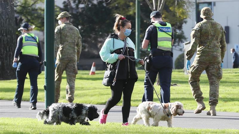 A woman walks her dogs in Fitzroy Gardens park as police and defence force officers patrol in Melbourne, Victoria, Australia [David Crosling/EPA]