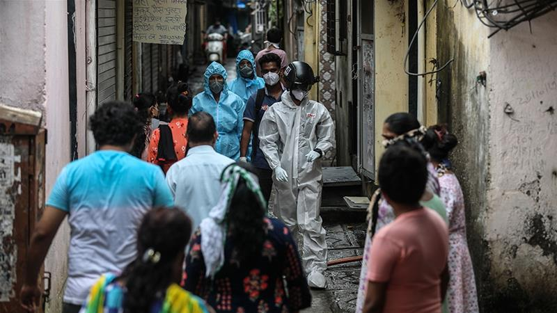 Health workers conduct thermal screening of residents of a slum in Mumbai [Divyakant Solanki/EPA]