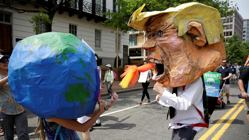 Protesters dressed as the earth and President Donald Trump pretend to fight during a climate march [File: Reuters]