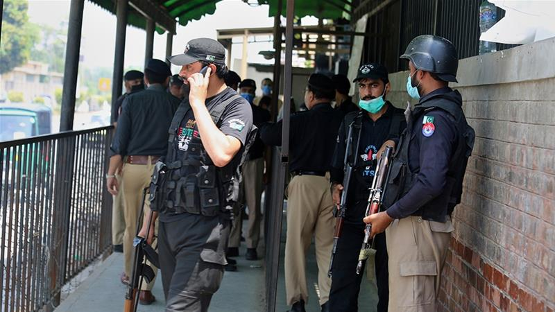 Police officers gather at an entry gate of Peshawar's district court following the killing of Tahir Ahmad Naseem [Muhammad Sajjad/AP]