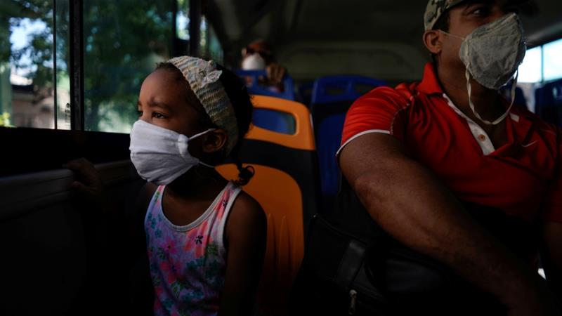Jenifer Reyes, 5, sits in a bus beside her father on Friday in Havana, Cuba  as coronavirus lockdowns eased and residents were able once again to use public transport, go to the beach and enjoy the city's famed Malecon seafront drive [Alexandre Meneghini/Reuters]
