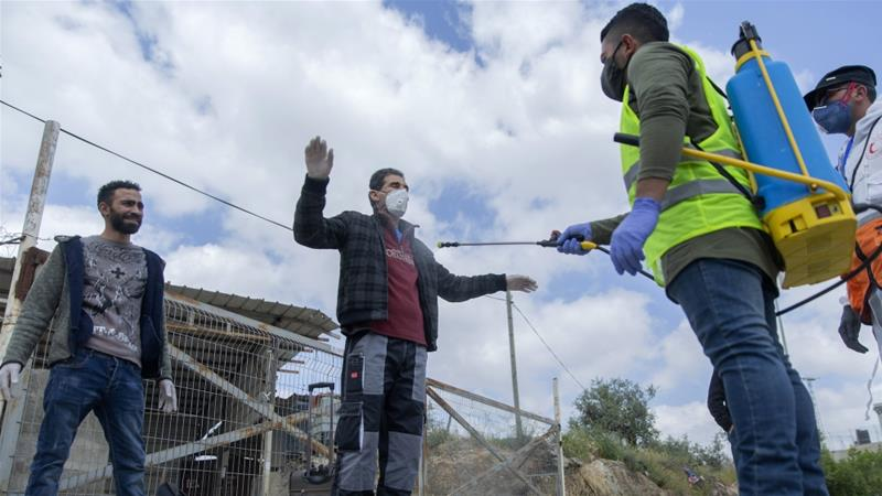A Palestinian paramedic disinfects labourers to help contain the coronavirus as they exit an Israeli army checkpoint, in occupied West Bank, April 7, 2020 [Nasser Nasser/AP Photo]