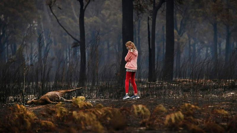 Mark Tregellas's daughter takes in the scene after Australia's worst-ever bushfires tore through her hometown of Mallacoota over the New Year [David Cairn/Al Jazeera]