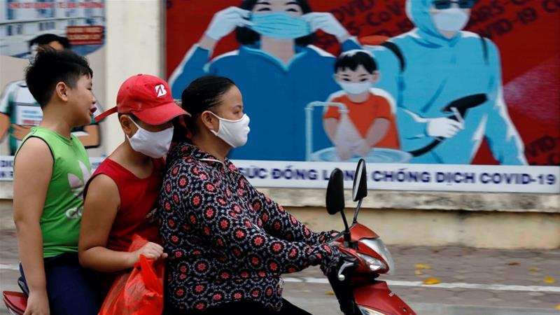 A woman wears a protective mask as she drives past a banner promoting prevention against the coronavirus in Hanoi, Vietnam, which reported its first two COVID-19 related deaths on Friday [File: Kham/Reuters]