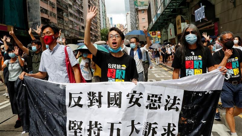 Pan-democratic legislator Eddie Chu Hoi-dick (L), Vice convener for Hong Kong's Civil Human Rights Front Figo Chan, and activist Leung Kwok-hung (R), march at the anniversary of Hong Kong's handover to China from Britain [File: Tyrone Siu/Reuters]