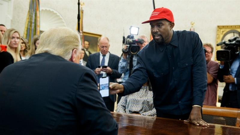 Kanye West shows United States President Donald Trump a photograph of a hydrogen plane during a meeting at the White House in 2018 [File: Evan Vucci/AP]