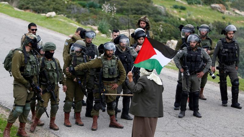 A Palestinian man stands in front of Israeli forces during a protest against Israeli settlements in the Israeli-occupied West Bank on February 25, 2020 [File: Reuters/Raneen Sawafta]