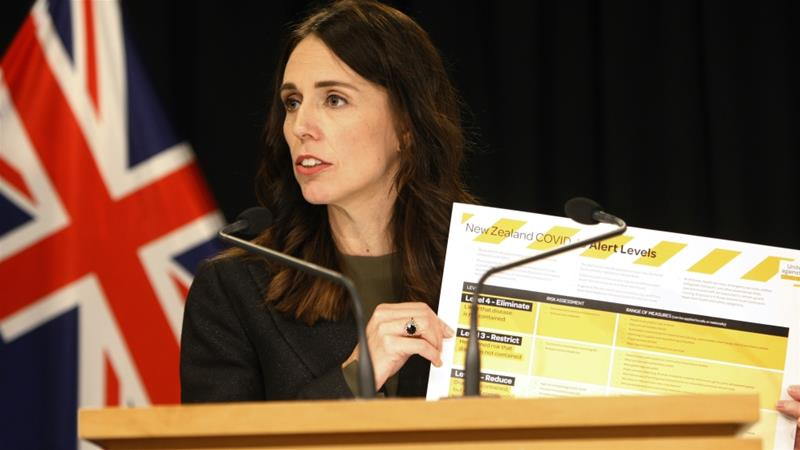 New Zealand Prime Minister Jacinda Ardern holds up a card showing a new alert system for COVID-19, on March 21, 2020, in Wellington, New Zealand [AP Photo/Nick Perry]