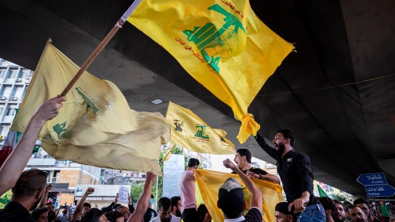 Hezbollah and Amal supporters wave Hezbollah and Iranian flags as they shout slogans against Israel and US during a protest in Beirut [File: Hassan Ammar/AP]