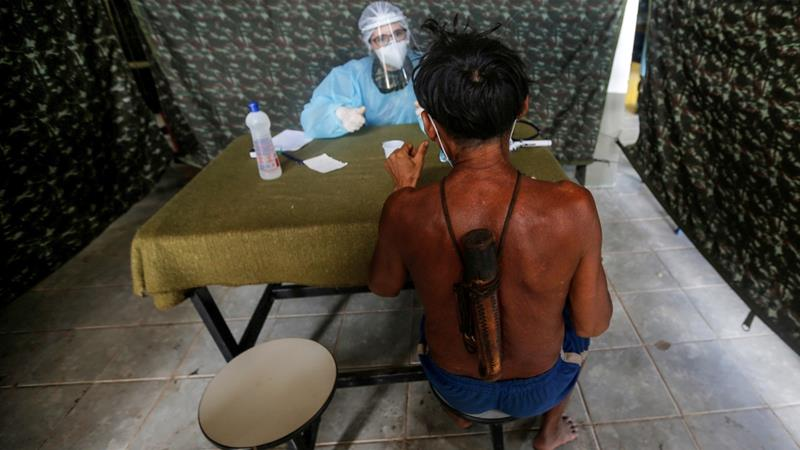 A member of the Brazilian Armed Forces medical team examines a man from the Indigenous Yanomami ethnic group, amid the spread of the coronavirus [Adriano Machado/Reuters]
