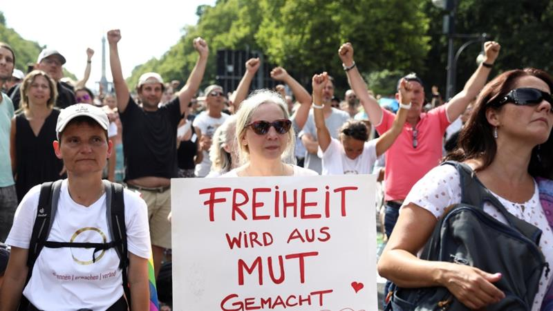 A demonstrator in Berlin holds a placard that reads 'freedom is made out of courage' during anti-coronavirus restriction demonstrations [Christian Mang/Reuters]