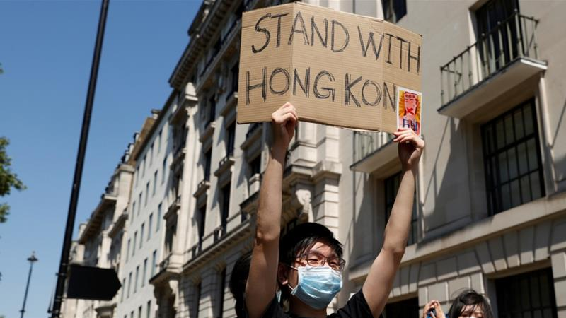 A man wearing a face mask holds up a placard during a protest against Hong Kong's deteriorating freedoms outside China's embassy in London, UK [John Sibley/Reuters]