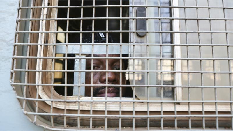 Hopewell Chin'ono seen through the window of a prison truck upon his arrival at the Harare court for his bail ruling [Tsvangirayi Mukwazhi/AP Photo]