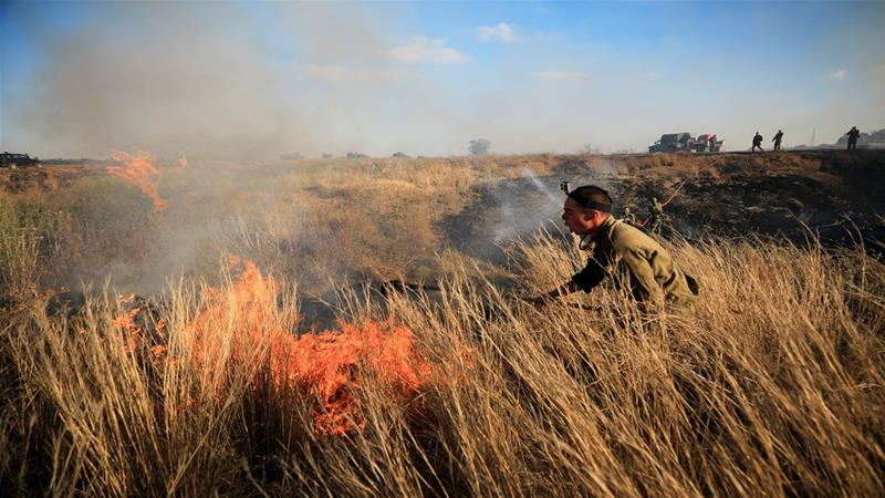 Israeli soldiers try to extinguish a blaze after balloons loaded with flammable materials were sent from Gaza [Reuters]