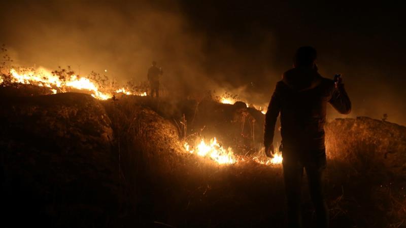 Um homem usa seu telefone perto de um incêndio na aldeia de Houla, perto da fronteira entre o Líbano e Israel, no sul do Líbano [Aziz Taher / Reuters]