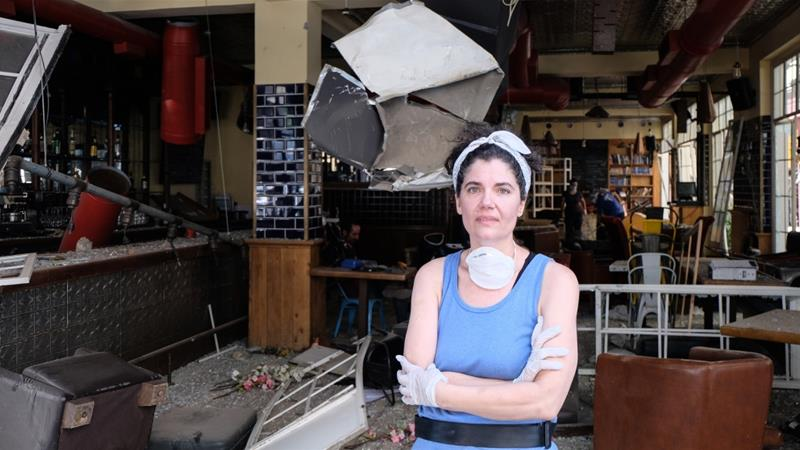 Naila Saba stands in front of her destroyed bar and bookstore in the Mar Mikhail neighbourhood in Beirut [Timour Azhari/Al Jazeera]