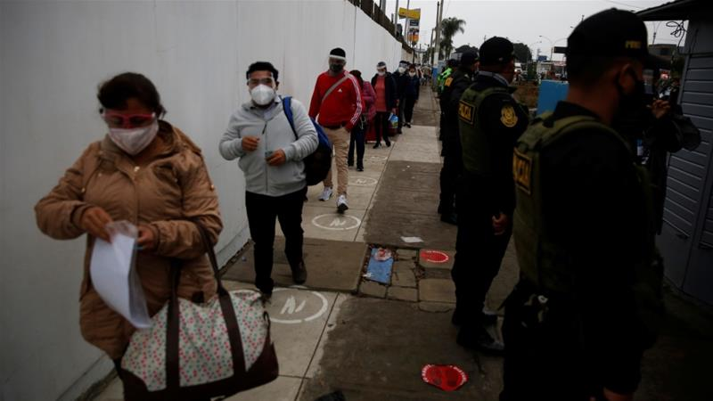 Passengers practice social distancing as they stand in line before entering the airport in Lima, Peru [File: Sebastian Castaneda/Reuters]