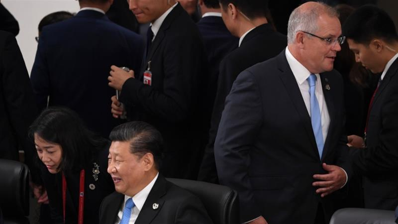 Australia's Scott Morrison, standing, walks past China's Xi Jinping during the G20 leaders' meeting in Japan last year [File: Lukas Coch via EPA]