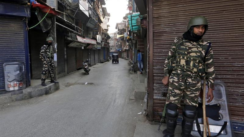 Indian security force personnel stand guard in front closed shops in a street in Srinagar, October 30, 2019 [File: Reuters/Danish Ismail]