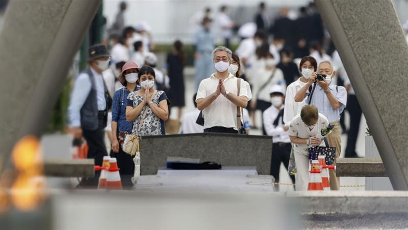 People pray in front of the cenotaph for the victims of the 1945 atomic bombing in Hiroshima [Kyodo via Reuters]