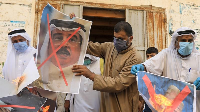 Palestinian men burn the exed out portraits of the Bahraini king, US president and the Israeli PM during a protest in Deir al-Balah in central Gaza Strip [Mahmud Hams/AFP]