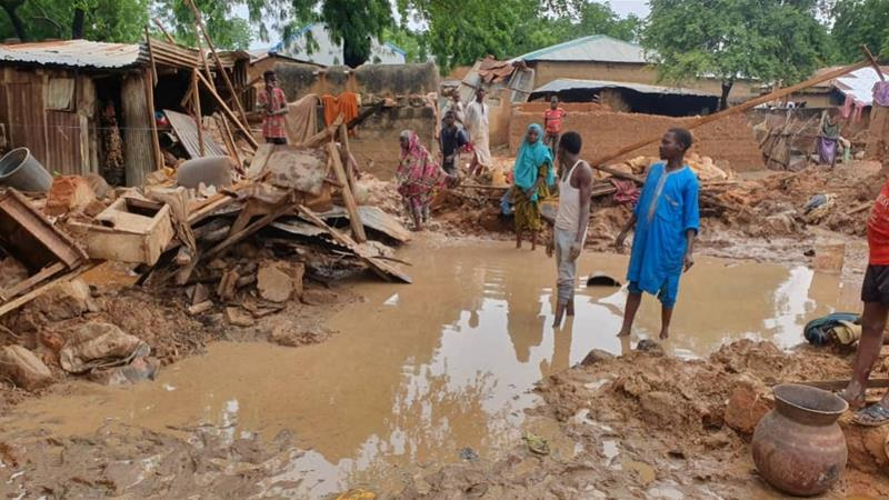People stand outside after their houses were destroyed following heavy rains in Kebbi state, Nigeria [File: Reuters]