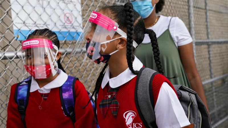 Students wear protective masks as they arrive for classes at the Immaculate Conception School while observing COVID-19 prevention protocols in New York City, the United States [File: John Minchillo/AP Photo]