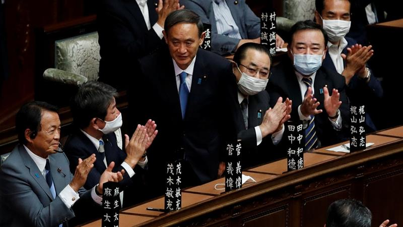 Japanese lawmakers applaud newly-elected Prime Minister Yoshihide Suga after he won a vote in parliament [Kim Kyung-Hoon/Reuters]