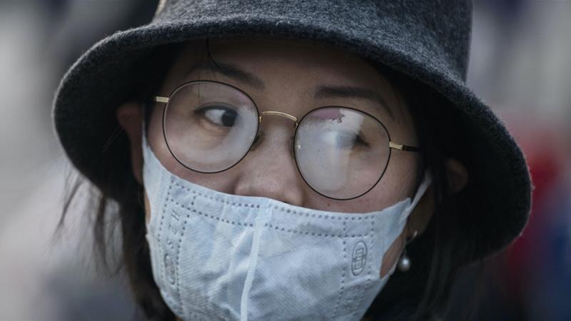 Kacamata seorang wanita berkabut saat mengenakan masker pelindung di Stasiun Beijing di China [File: Kevin Frayer / Getty Images]