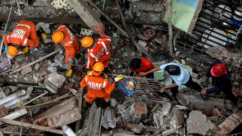Rescue workers search for survivors from the debris of the three-storey residential building in Bhiwandi [Francis Mascarenhas/Reuters]