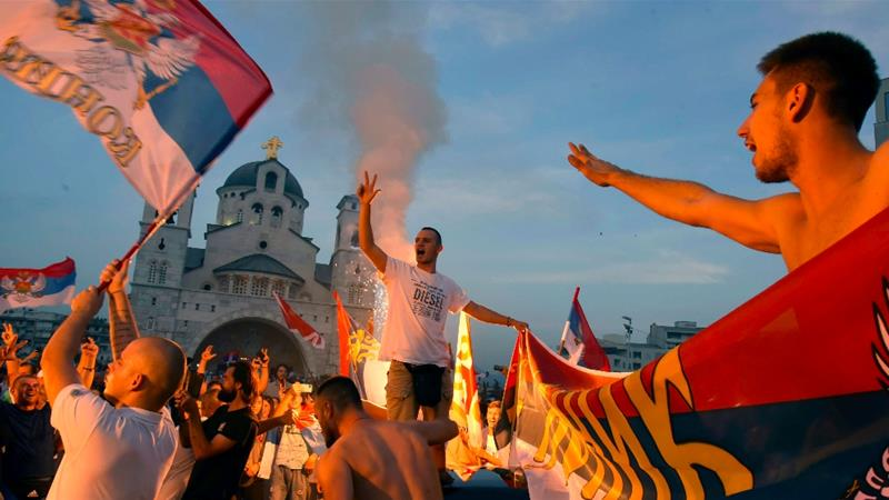 Opposition supporters celebrate after parliamentary elections in front of the Serbian Orthodox Church of Christ's Resurrection in Podgorica, Montenegro [Risto Bozovic/AP]