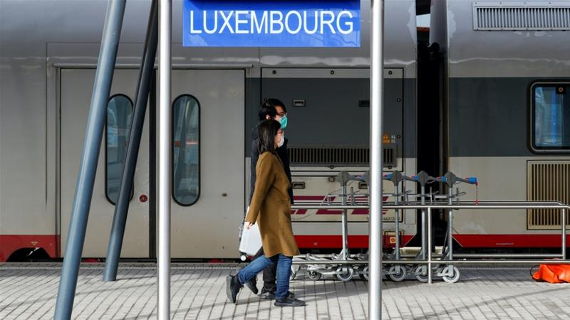 Tourists wearing masks walk on a platform at a railway station in Luxembourg, which last year launched a 10-step framework to implement the UN's 17 sustainable development goals [File: Francois Lenoir/Reuters]