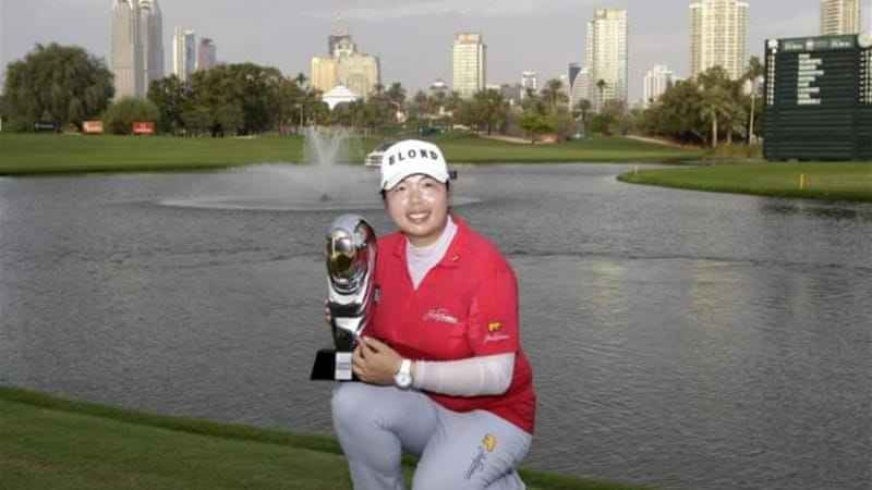Feng of China celebrates with her trophy after running away with victory in the Dubai Ladies Masters [AP]