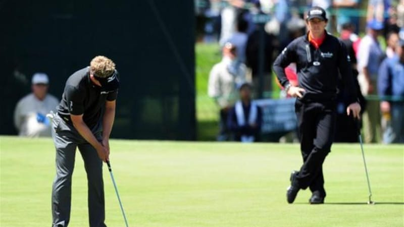 World number one Donald (putting) had miserable day as too did reigning champ McIlroy (watching) [AFP]