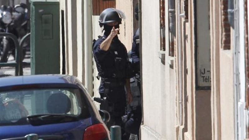 French police officers cordoned off the street where a man had taken four hostages in a bank, in Toulouse [EPA]