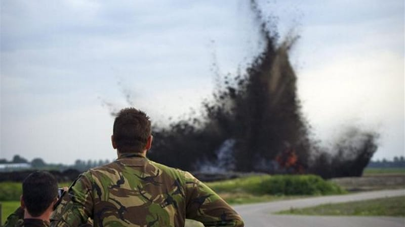 Dutch soldiers look on as a World War II bomb is detonated in a controlled explosion at Schiphol airport [EPA]