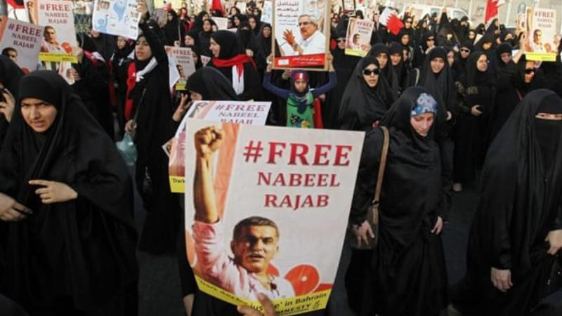 Protesters carry posters of activist Nabeel Rajab, who was sentenced to three years in prison [EPA]