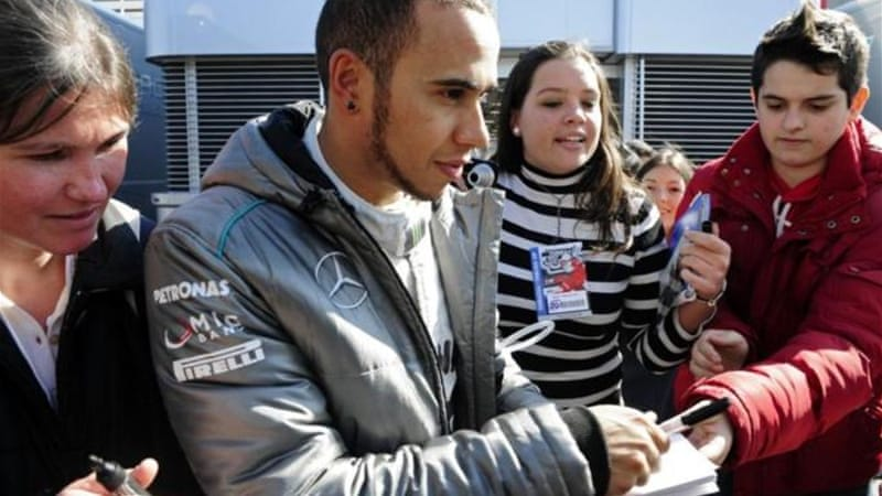 Mercedes driver Lewis Hamilton takes some time out of practice to sign autographs for fans [AP]
