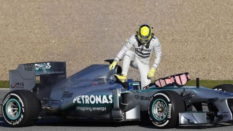 Rosberg gets out of his Mercedes as smoke billows from the car during testing [Reuters]